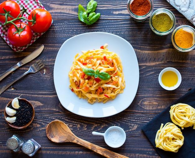 Tagliatelles à la tomate et au basilic, faites à la maison sur une table en bois