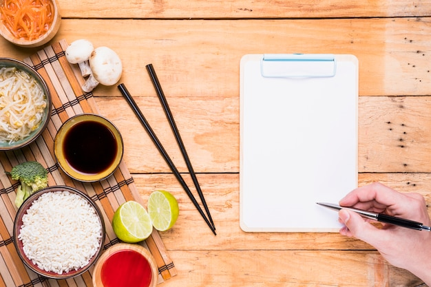 Tai nourriture avec la main d'une personne écrit sur le presse-papiers avec stylo sur le bureau en bois