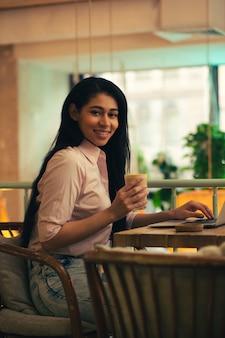 Taille d'une belle jeune femme souriante à la caméra alors qu'elle était assise dans un café avec un ordinateur portable et tenant un verre de café