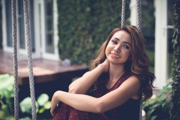 Taille coup de joyeuse fille assise sur une balançoire et regardant de côté rêveusement