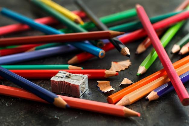 Un taille-crayon et des crayons de couleur sur fond sombre