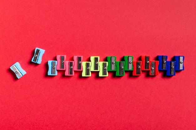 Taille-crayons colorés sur une table rouge