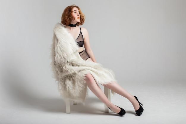 Taille curvy plus femme modèle cheveux roux en lingerie et veste au studio fond blanc