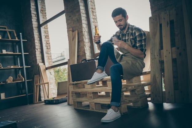 Taille du corps pleine longueur homme positif joyeux en chemise à carreaux discutant avec un ami au téléphone, boire de la bière