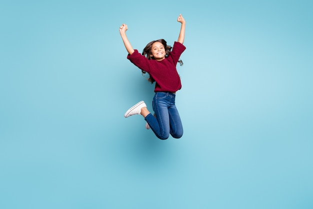 Taille du corps sur toute la longueur photo de fille frisée joyeuse positive sautant portant des jeans denim souriant à pleines dents isolé fond de couleur bleu vif