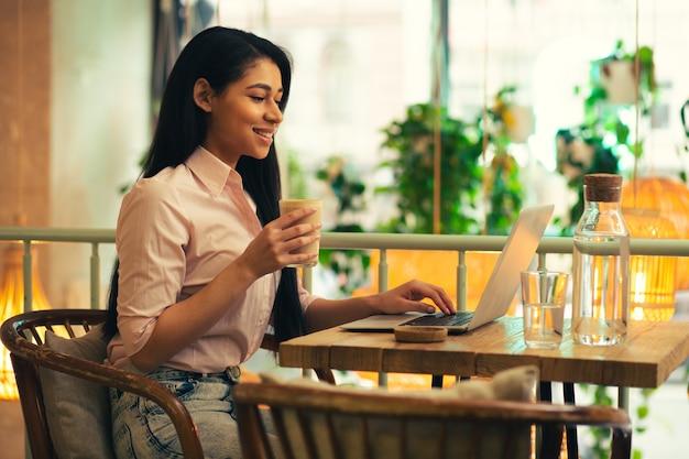 Taille d'un étudiant confiant aux cheveux longs tenant un verre de latte et souriant tout en utilisant son ordinateur portable dans le café