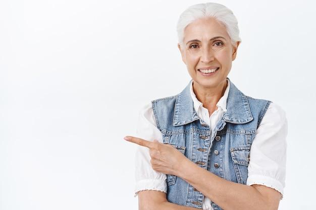 Taille femme âgée caucasienne moderne et élégante avec des cheveux gris peignés, souriant joyeusement avec une expression heureuse et satisfaite, pointant le doigt vers la gauche, donner des conseils, montrer un lien promotionnel ou cadeau