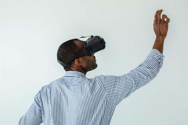 Taille de l'homme d'affaires afro-américain professionnel écrit sur le tableau tout en utilisant un appareil vr