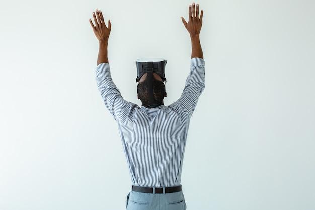 Taille d'un homme afro-américain agréable tenant les mains tout en utilisant des lunettes vr