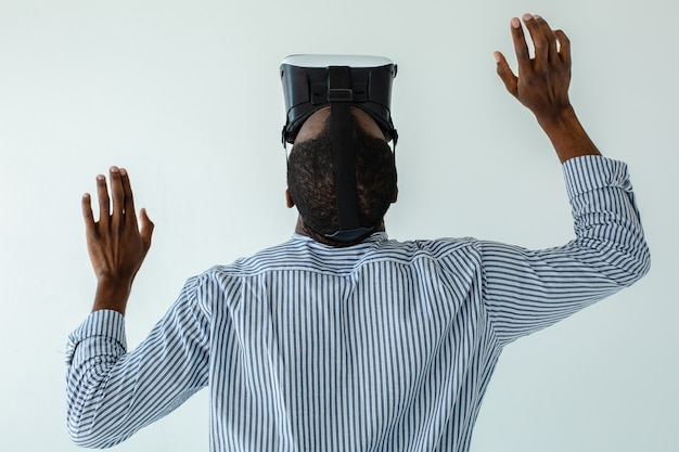 Taille d'un homme afro-américain agréable tenant sa tête tout en testant des lunettes vr
