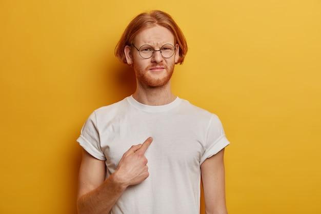 La taille d'un homme barbu mécontent avec une coiffure au gingembre se pointe sur lui-même, me demande pourquoi, porte un t-shirt blanc décontracté, des lunettes, pose contre un mur jaune, étant dérangé et malheureux