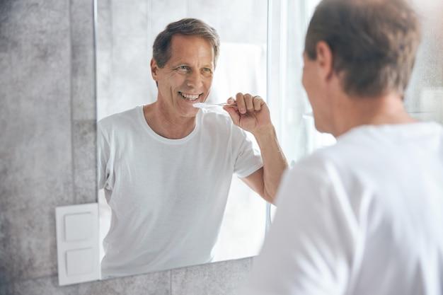 Taille homme avec une brosse à dents souriant à lui-même dans le miroir