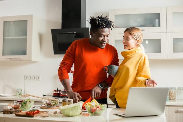 Taille de l'homme joyeux couper des légumes dans la cuisine tandis que sa petite amie positive pointant vers l'écran de l'ordinateur portable