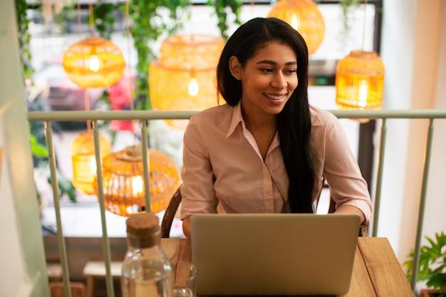Taille d'un jeune étudiant heureux assis seul dans le café et regardant au loin avec un sourire tout en ayant un ordinateur portable moderne devant elle
