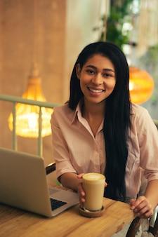 Taille d'une jeune femme aux cheveux longs assise à la table du café avec un ordinateur portable moderne devant elle et souriant tout en touchant un verre de latte