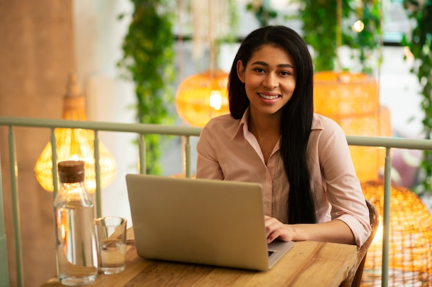 Taille d'une jeune femme calme et heureuse souriante tout en travaillant sur son ordinateur portable dans un café avec une carafe d'eau en verre près de son appareil