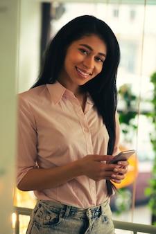 Taille d'une jeune femme heureuse debout avec un smartphone dans les mains et souriant à la caméra