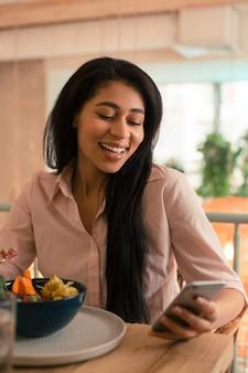 Taille d'une jeune femme heureuse souriante la bouche ouverte et regardant l'écran de son smartphone tout en prenant un repas dans un café