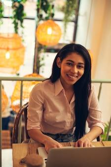 Taille d'un jeune spécialiste confiant assis dans le café avec un ordinateur portable moderne sur la table et souriant joyeusement