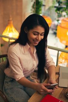 Taille d'une jolie dame en jeans et chemisier souriante en lisant des messages sur son smartphone