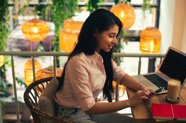 Taille d'une jolie femme calme utilisant son smartphone moderne assis à la table du café avec un ordinateur portable et du café dessus