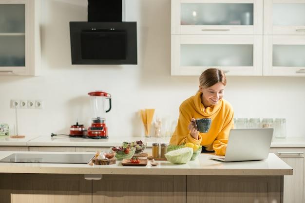 Taille de joyeuse jeune femme souriante tout en regardant les éboulis de son ordinateur portable dans la cuisine avec de la nourriture sur la table et une tasse de thé dans ses mains