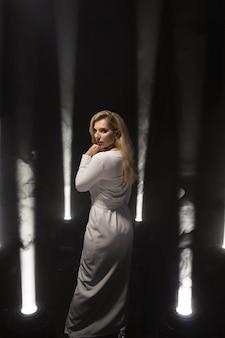 Taille plus blonde luxueuse avec de longs cheveux blancs posant dans une longue robe blanche sur une scène sombre dans la fumée avec la lumière.