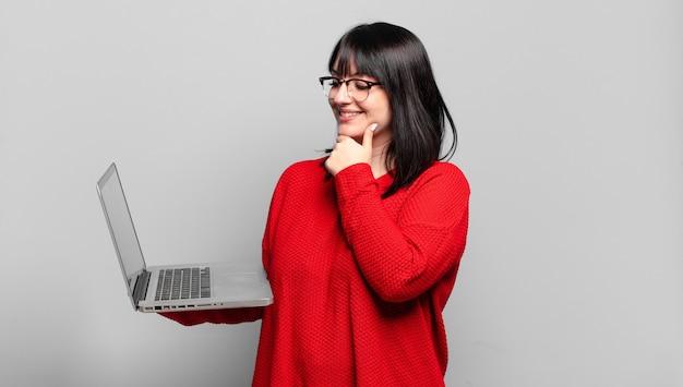 Taille plus jolie femme souriante avec une expression heureuse et confiante avec la main sur le menton, se demandant et regardant sur le côté