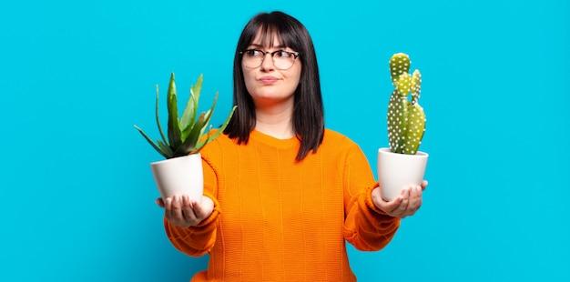 Taille plus jolie femme tenant un cactus.