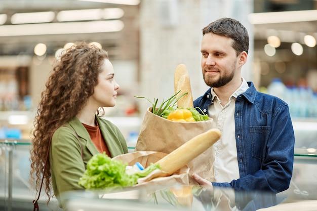 Taille portrait de couple moderne tenant des sacs en papier avec des produits d'épicerie tout en profitant du shopping dans un supermarché