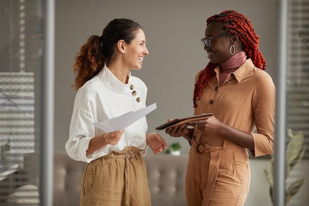Taille portrait de deux jeunes femmes d'affaires prospères souriant joyeusement en se regardant tout en se tenant debout dans l'intérieur de bureaux modernes, espace copie