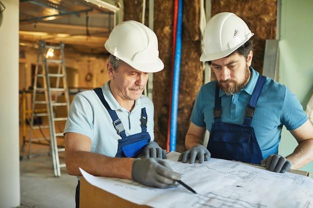 Taille portrait de deux travailleurs de la construction portant des casques tout en regardant les plans d'étage lors de la rénovation de la maison, copiez l'espace
