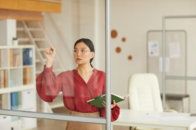 Taille portrait de femme d'affaires asiatique moderne écrit sur mur de verre lors de la planification du projet au bureau, espace copie
