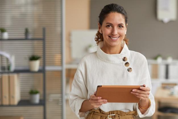 Taille portrait de femme d'affaires moderne élégante tenant la tablette et regardant la caméra avec des écouteurs sans fil en se tenant debout dans le bureau, copiez l'espace