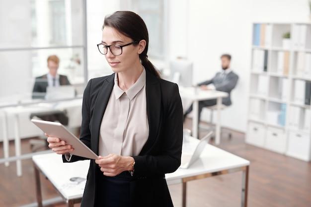 Taille portrait de femme chef d'entreprise à l'aide de tablette numérique tout en se tenant au bureau, copiez l'espace