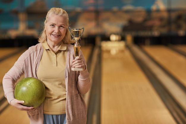 Taille portrait d'une femme mûre souriante tenant un trophée et regardant la caméra en se tenant debout dans un bowling après avoir remporté le match, espace de copie