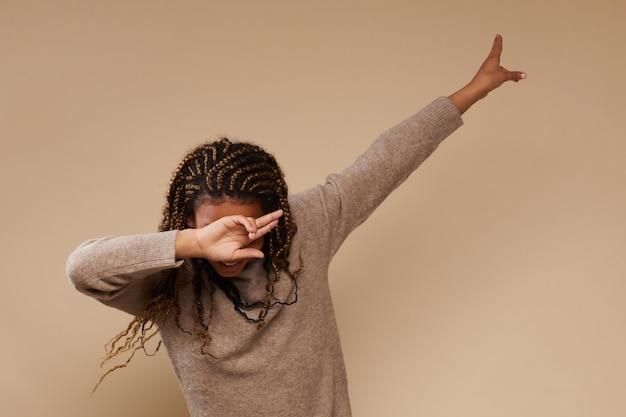 Taille portrait de fille afro-américaine insouciante faisant des gestes en studio, copiez l'espace
