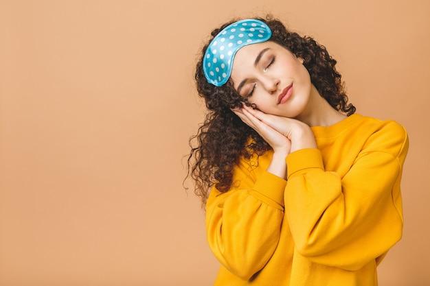 Taille portrait de gaie jeune belle fille souriante bouclée dans un masque de sommeil. isolé sur fond beige.