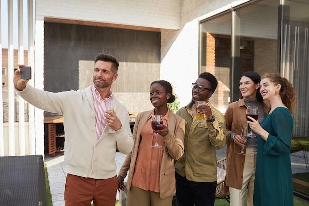 Taille portrait de groupe multiethnique d'amis prenant une photo de selfie tout en profitant de la fête debout sur la terrasse extérieure