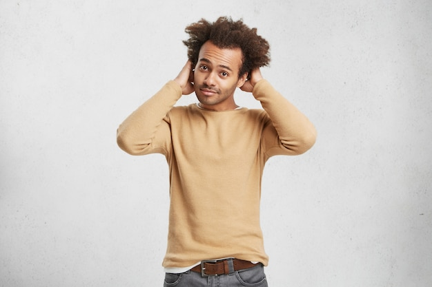 Taille portrait d'homme attrayant bouclé élégant avec une peau foncée porte des vêtements à la mode