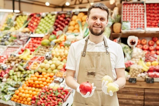 Taille portrait d'homme barbu portant un tablier et souriant tout en vendant des fruits et légumes frais au marché de producteurs