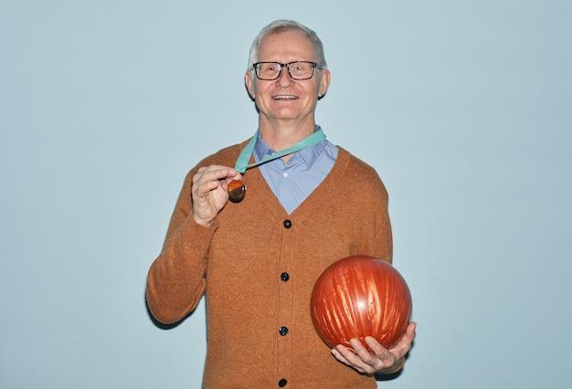 Taille portrait d'un homme senior souriant tenant une boule de bowling et portant une médaille souriant à la caméra en se tenant debout sur fond bleu, espace pour copie
