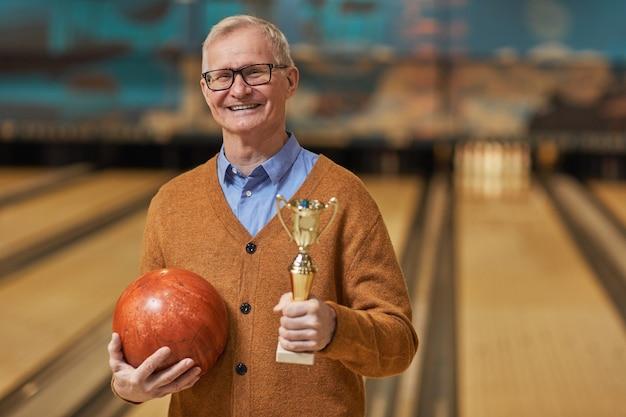 Taille portrait d'un homme senior souriant tenant un trophée et une boule de bowling tout en posant au bowling après avoir remporté le match, espace de copie