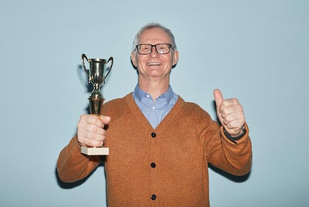 Taille portrait d'un homme senior souriant tenant un trophée et regardant la caméra en se tenant debout sur fond bleu, espace pour copie
