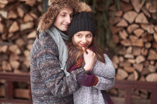 Taille portrait d'insouciant jeune homme et femme embrassant et souriant. ils sont debout dans la forêt d'hiver et regardant la caméra avec bonheur