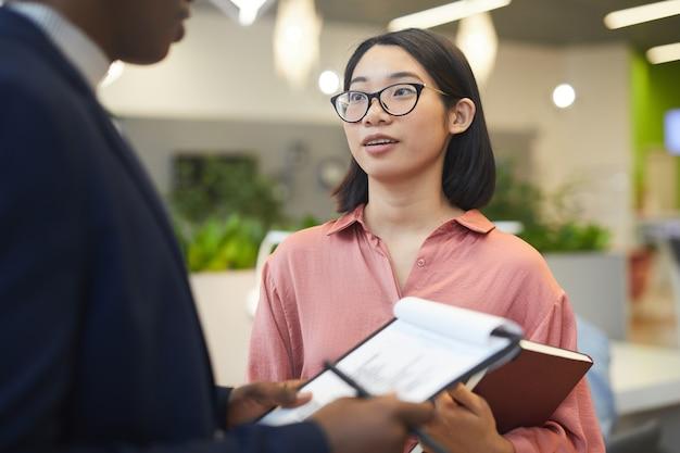 Taille portrait de jeune femme d'affaires asiatique parlant à son partenaire tout en discutant du projet de travail
