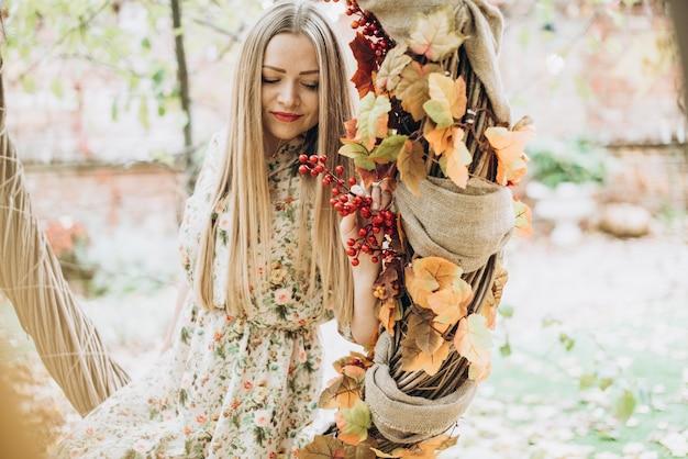 Taille portrait de la jeune femme blonde belle caucasienne assise dans une grande couronne d'automne ou une balançoire et regardant ailleurs tout en posant