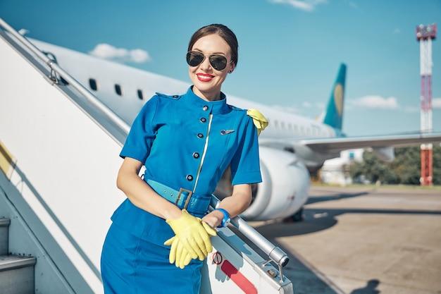 Taille portrait d'une jeune femme heureuse en uniforme bleu et lunettes de soleil debout sur l'escalier de l'avion de passagers