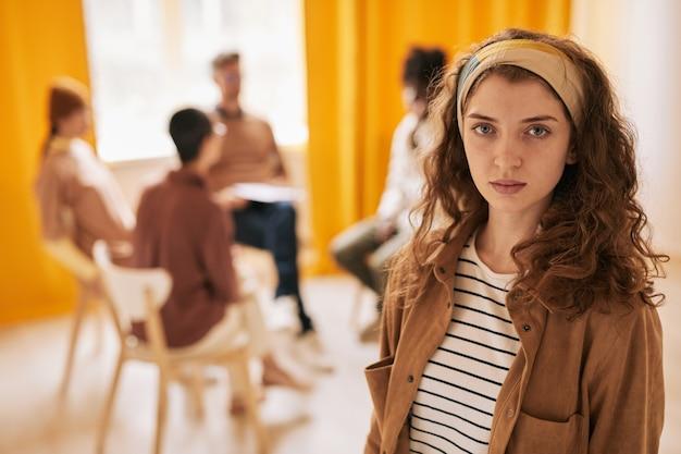 Taille portrait d'une jeune femme regardant la caméra pendant une séance de thérapie dans un groupe de soutien, espace de copie