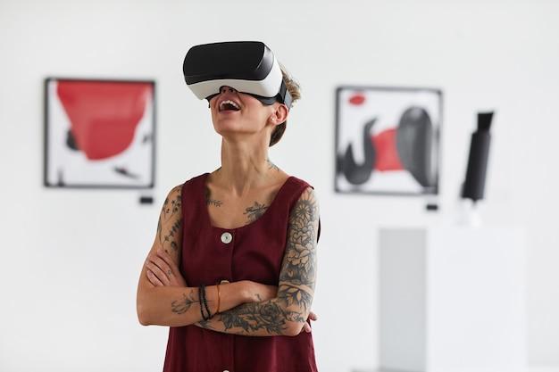 Taille portrait de jeune femme tatouée portant des vêtements de réalité virtuelle tout en profitant d'une expérience immersive à l'exposition de la galerie d'art moderne,